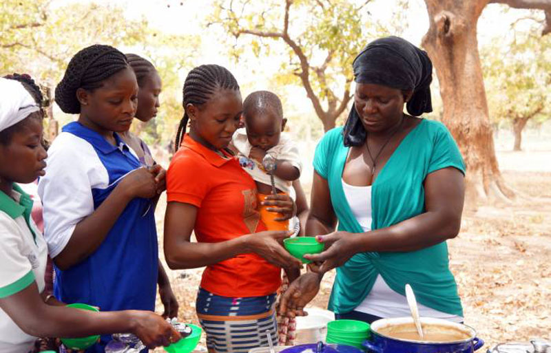 A woman serves porridge after demonstrating how to make it in Noungou village, Burkina Faso, March 23, 2017.